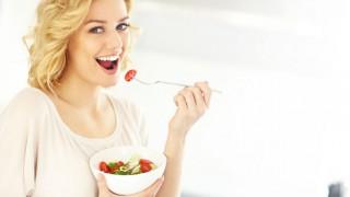 Eine junge Blondine isst einen Salat