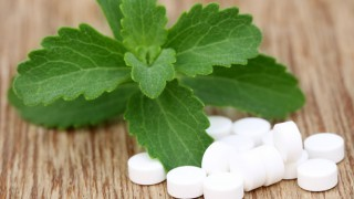 Ein Stevia-Blatt mit einigen Dragees