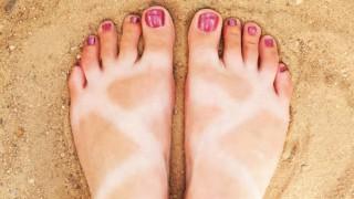 Von der Sonne im Muster gebräunte Füße